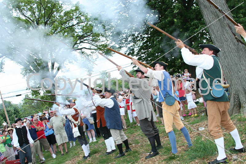 Minutemen discharge their muskets.