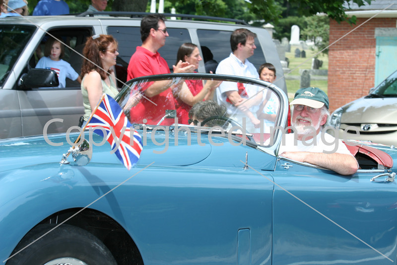 With the Union Jack on his mirror, Dave Durrant and his wife Pam drive their convertible in the Fourth of July parade.