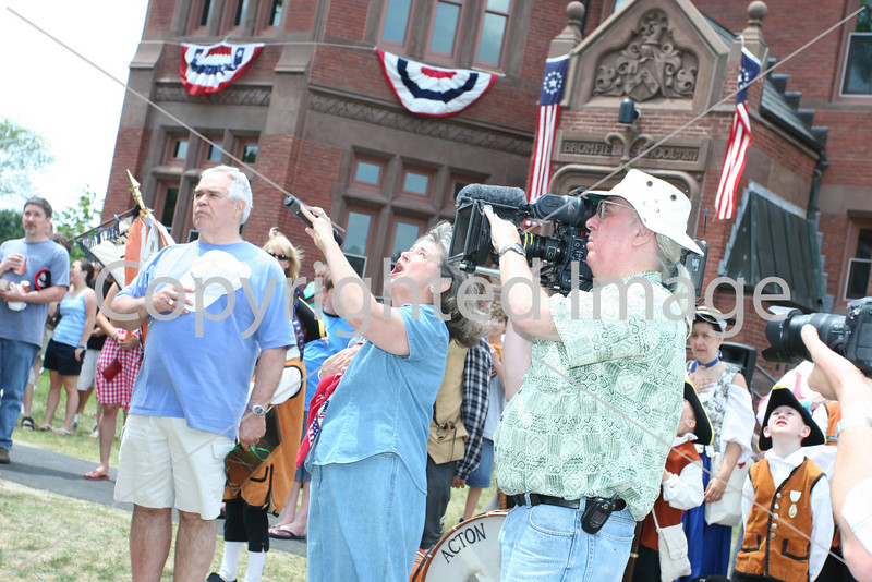 Hat in hand, Ed Carter listens as Kathy Brule sings the National Anthem as cameraman Boyd Estes captures the scene for PBS.
