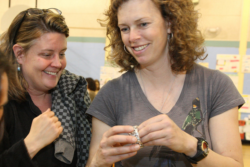 Sarah Connolly and Caroline Fish check out some jewelery made from plastic bags at the Earth Day Fair held at the elementary school last Tuesday.