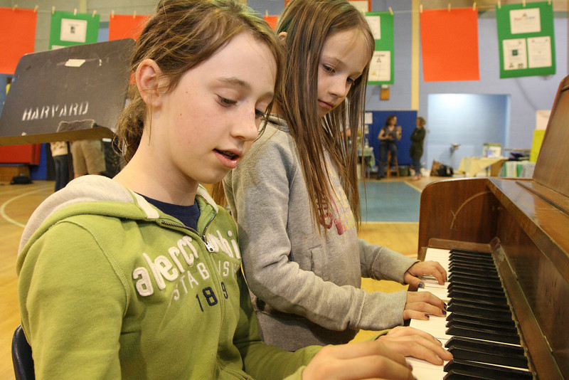 Emily (left) and Rachel Ferguson play at duet on the piano at the Earth Day Fair held at the elementary school last Tuesday.