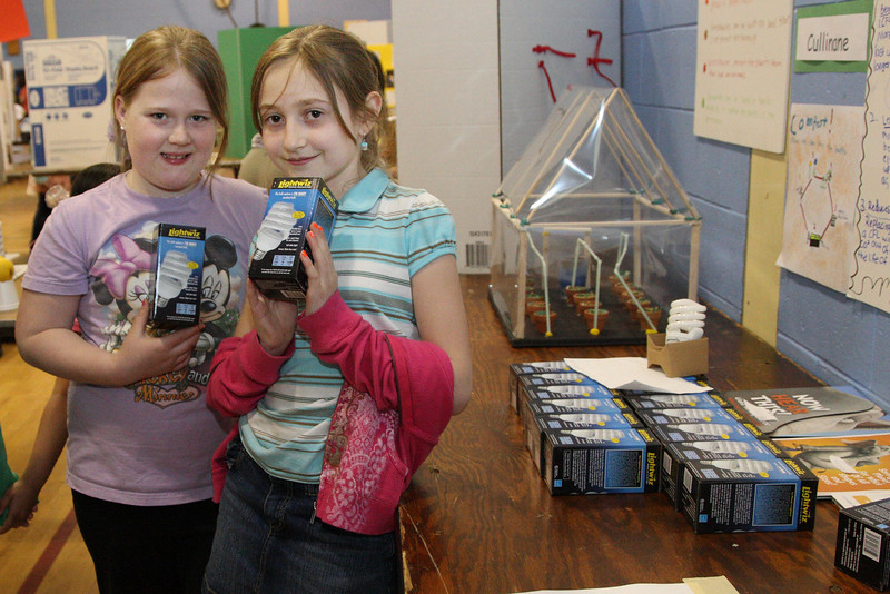 Allison Milliken and Gwyneth Evans hand out CFLs at their demonstration of how much energy is saved by replacing incandescent lightbulbs with CFLs. The bulbs were donated by National Grid after the gilrs sent a written request to the company.