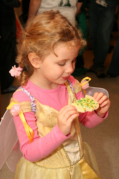 Three-year old Sarah Peterson, granddaughter of John and Gail Ownings, gingerly holds a Halloween cookies.