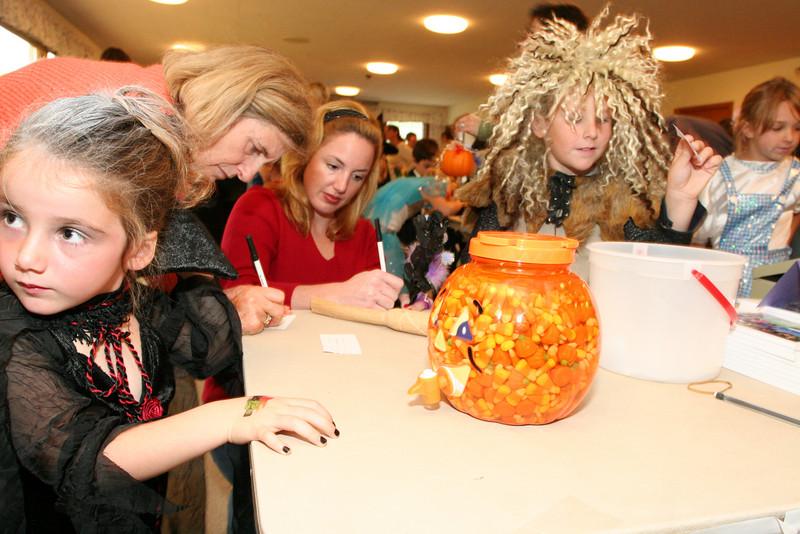 Autumn Femino McNamara, Mina Femino, Kelly McNamara, and Charlie Bardenheuer take a guess as to how many candy corn are in the pumpkin.