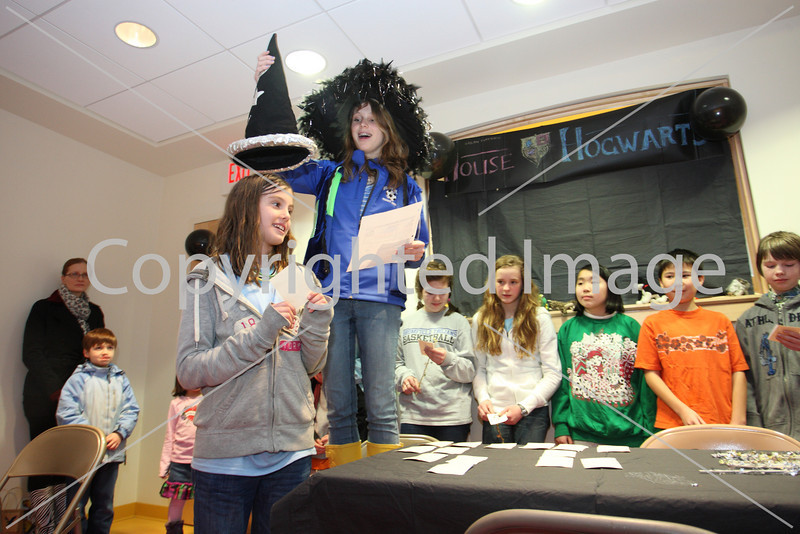 Alexandra Saganich stands under the sorting hat held by Kara Kennedy at the Girl Scouts Harry Potter party held at the library on Mar. 16. (Photo by Lisa Aciukewicz)