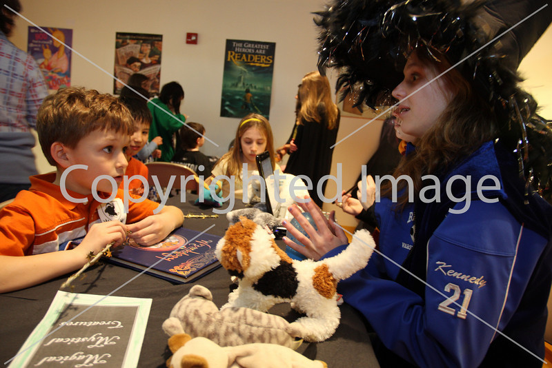 Lucas Castro listens intently as Kara Kennedy tells him his horoscope at the Girls Scouts Harry Potter party at the library on March 16.