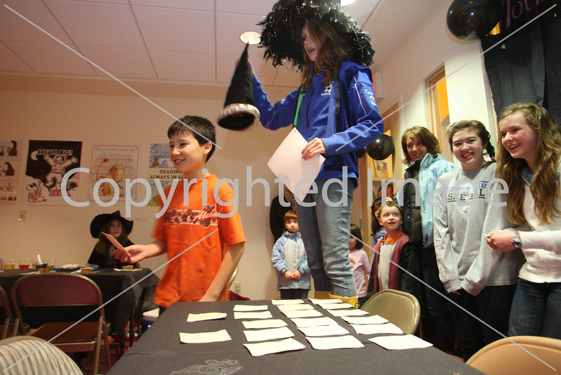 Evan Bilafer stands under the sorting hat held by Kara Kennedy at the Girl Scouts Harry Potter party held at the library on Mar. 16. (Photo by Lisa Aciukewicz)