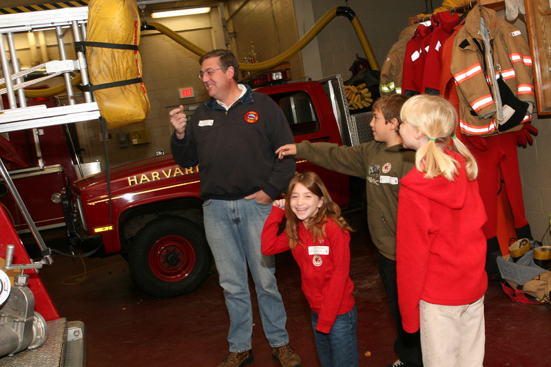Firefighter Alan Specht tells Arielle Sclar, Chris West, and Kate Toll about the engines in the fire station.