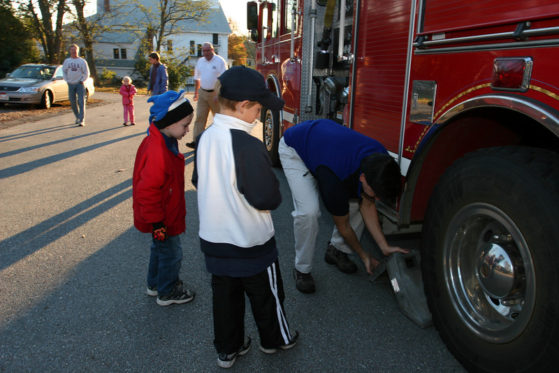 Will Squire and Sam Rosenfield watch as Bill Barton places a block behind the wheel of a fire engine.
