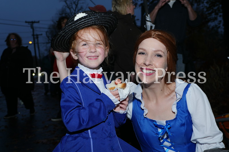 Harvard Halloween 2019 Windy, rainy and warm.<br /> <br /> A windblown Belle (Maren Caulfield) and Mary Poppins (Ada Caulfield) recharge with a hot dog from the Lion's Club