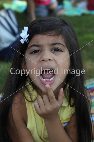 Incoming kindergartener Asha Khurana shows off where she had two teeth pulled the day before the picnic.