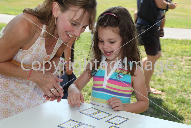 Becky Moran (left) helps her daughter Abigale look for her name tag at the kindergarten picnic.