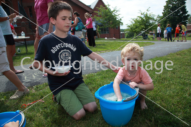 Luke Jones watches over his brother Cole as he fishes for a lost pipe cleaner in a bucket of bubbles.