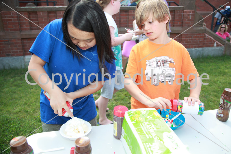 Grace Young and Caden Bishop add toppings to their sundaes.