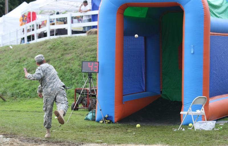 Steven Connoly, a National Guardsman out of Devens, throws a pitch at the Lions Fall Festival.