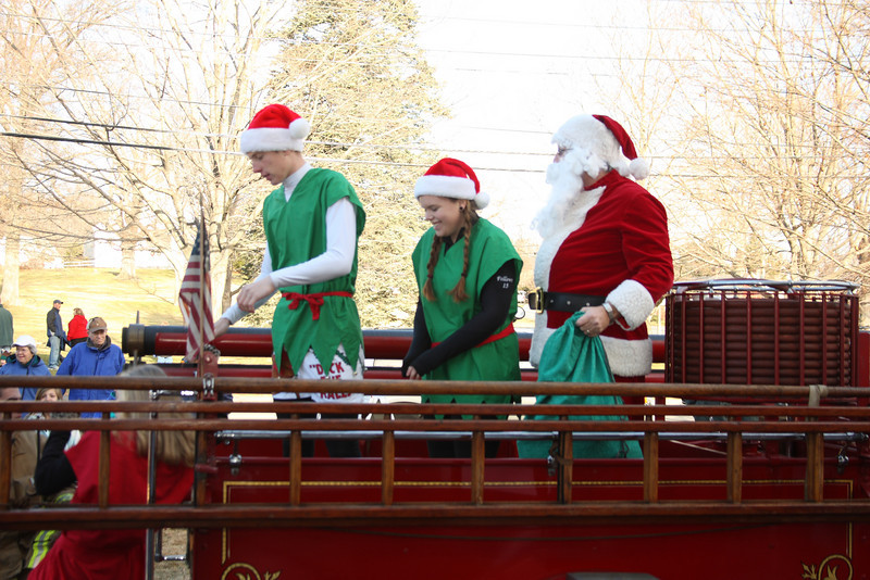 Santa's helpers Caleb Frost and Anna Fellows lead Santa off the firetruck after arriving at the Congregational church.