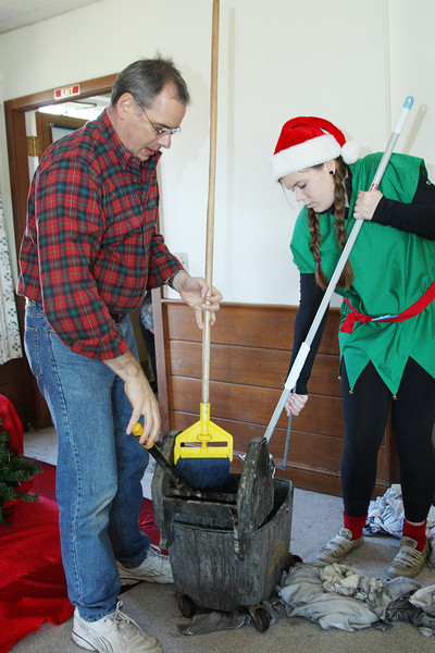 Reverend Greg Schmidt and Santa's helper Anna Fellows mop water off the floor of the Congregational church meeting room after a heating pipe burst just minutes before Lunch with Santa was to begin.