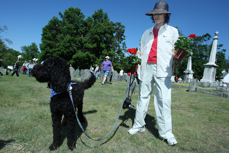 All dressed up and ready to go: Winston the goldendoodle and owner Julie Sniffen prepare to deliver geraniums to the graves of veterans.