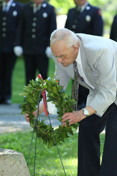 Roland Martineau places a wreath at Bellevue Cemetary during Memorial Day activities.