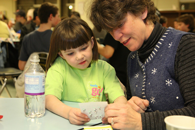 First-grader Bridgit Kennedy gets help with her card from mom Janice.