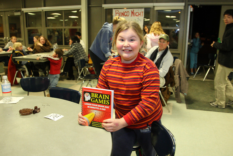 Maggie Gill shows off the book her mom won during family game night at Bromfield.