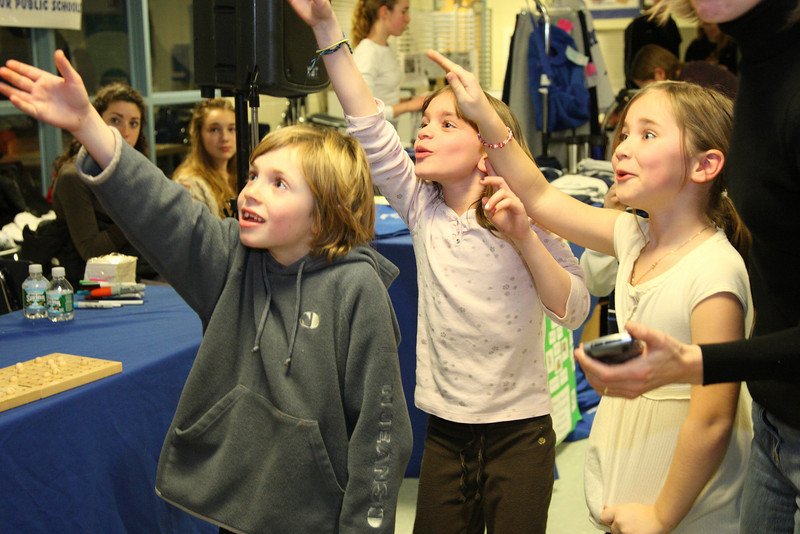 Gabe Sennott, Leila Grant, and Madison Drummey all reach for the microphone so that they can take a turn announcing the numbers in bingo during a family game night at Bromfield.