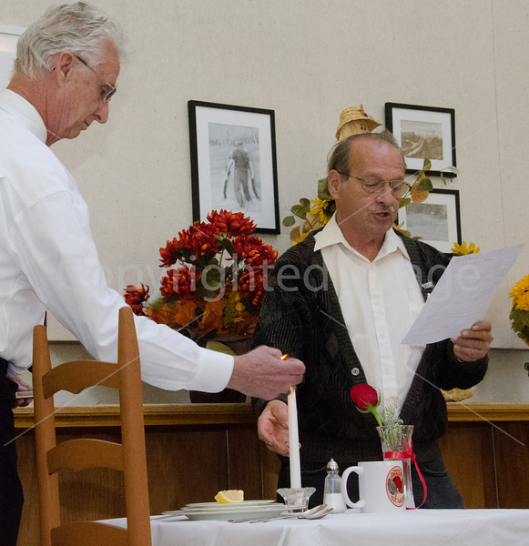 Don Green lights candle while Gregory Stirk reads POW/MIA description