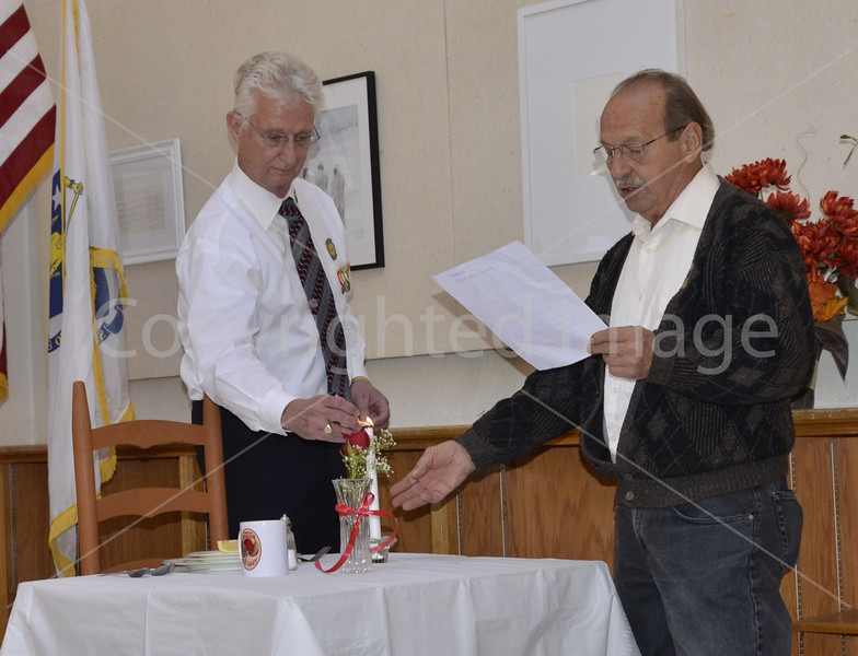 Don Green lights the candle while Gregory Stirk narrates the POW/MIA ceremony