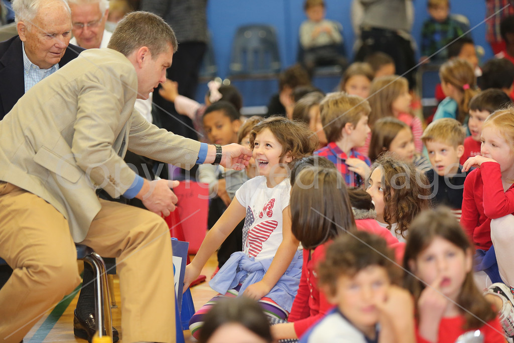 U.S. Marine Corps Sergeant John Knowles, who often performs at a magician at local children's events, pretends to pull a coin from Audrey Slavin's ear.