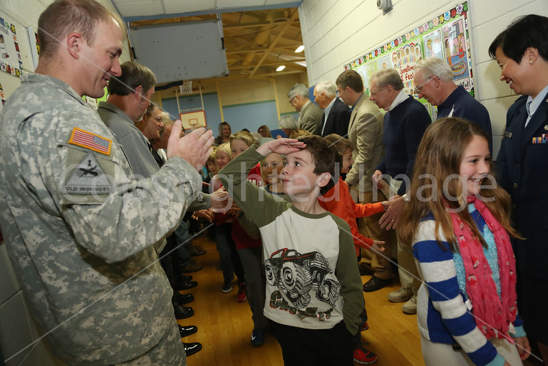 U.S. Army Captain David Gowel receives a salute from Jason Smith as he and Audrey Slavin leave Tuesday's Veterans Day assembly. This year children got the opportunity to thank veterans personally as they headed back to class.