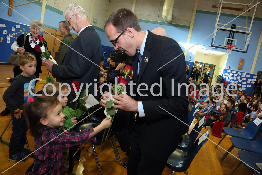 Veterans receive roses from their loved ones at a Veterans Day service at the Hildreth Elementary School, Nov. 10. From left: Cooper Green, Pat Sciple, Lydia Coyne, Louisa Coyne, Carl Sciple, Don Green, and Dennis Coyne. (Photo by Lisa Aciukewicz)