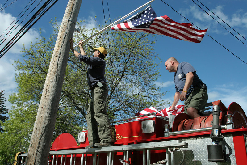 Bill Barton and Bill Mcelhaney place flags on telephone poles from atop engine 4 in preparation for the Memorial Day parade. The flags were purchased by the Fire Department to honor the late Al Rouvel.