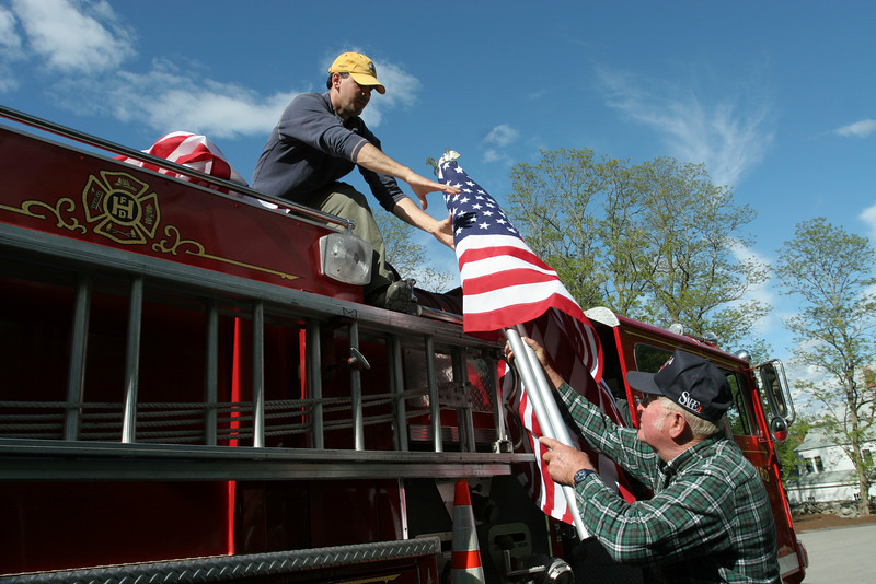 Bill Barton receives a flag from Warren Harrod as they load the fire truck to place falgs on the common. The fire department bought 30 flags to place on the Common as a tribute to the late firefighter Al Rouvel.