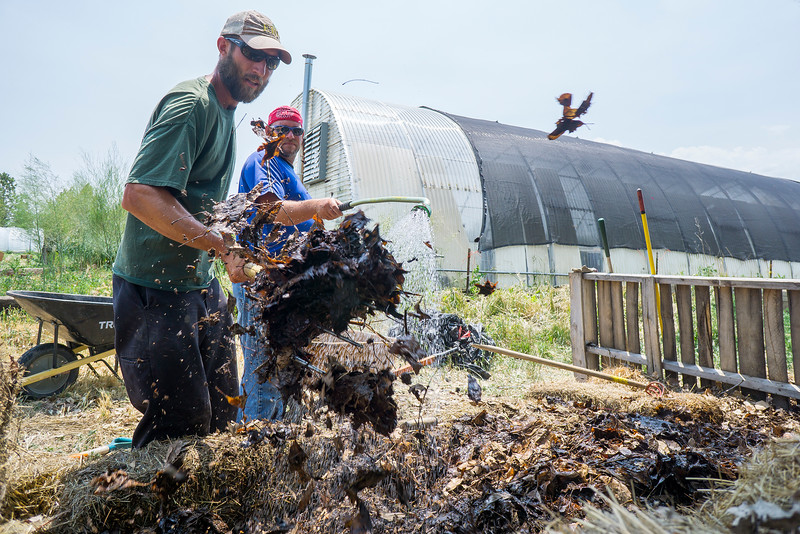 Kelly Ballantyne,left, churns the compost pit while Joe Sutton waters the underlayer on Tuesday June 21, 2016 at Harvest Farm. The compost has to be churned and stay wet in order for the worms to break down the material. <br /> <br /> Photo by Michael Ortiz/ Loveland Reporter-Herald