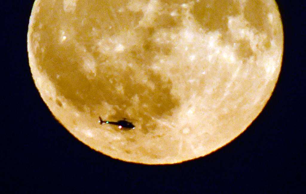 . A helicopter passes by the harvest moon as seen from Legion Park in Boulder, Colorado. The harvest moon as seen from Legion Park in Boulder, Colorado. Cliff Grassmick  Staff Photographer October 5, 2017