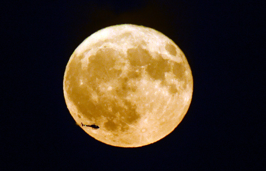 . A helicopter passes by the harvest moon as seen from Legion Park in Boulder, Colorado. Cliff Grassmick  Staff Photographer October 5, 2017