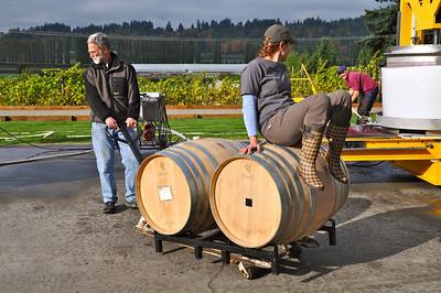 Intern Rebecca Weber plays counterweight to a barrel of wine.