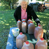 "Harvey Price, 93, talks about making cider for 80 years. Called a ""legendary beverage in Lunenburg"" he makes it with a press that is over 100 years old. Agnes Price, Harvey's wife of 66 years, puts out more cider for customers in their front yard on Thursday afternoon. SENTINEL & ENTERPRISE/JOHN LOVE"