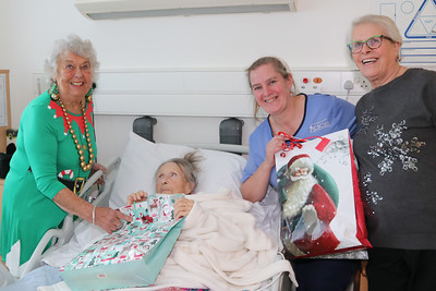 25 DEC 2019 – Pictured: Betty Holbrook MBE (Vice Chair, H&D Fellowship for the Sick) with patient Joann Smith,  Penny Townsend (HCA) and Sheena Parson (Hon Secretary, H&D Fellowship for the Sick) - Harwich & District Fellowship for the Sick Christmas Gifts – Trinity Ward, Harwich Fryatt Hospital, Dovercourt. – Photo Copyright © Maria Fowler 2019
