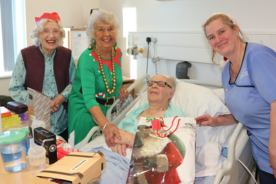 25 DEC 2019 – Pictured: Joyce Clarey, Betty Holbrook MBE (Vice Chair, H&D Fellowship for the Sick) with patient James Clarey and Penny Townsend (HCA) - Harwich & District Fellowship for the Sick Christmas Gifts – Trinity Ward, Harwich Fryatt Hospital, Dovercourt. – Photo Copyright © Maria Fowler 2019