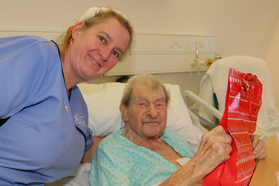 25 DEC 2019 – Pictured:  Health Care Assistant Penny Townsend with patient John Whittle - Harwich & District Fellowship for the Sick Christmas Gifts – Trinity Ward, Harwich Fryatt Hospital, Dovercourt. – Photo Copyright © Maria Fowler 2019