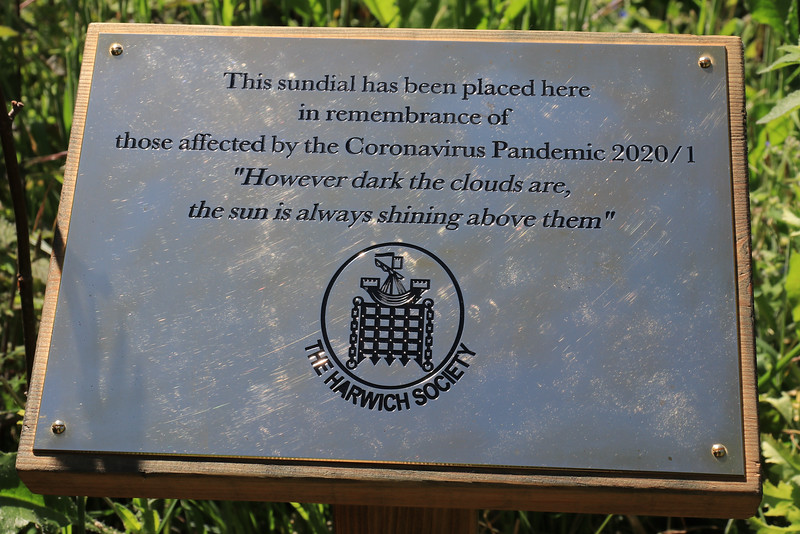 """13 JUN 2021 - Sundial at Bobbit's Hole Nature Reserve, in remembrance of those affected by the Coronavirus Pandemic 2020/21. 13 JUN 2021 - Photo Copyright © Maria Fowler 2021<br /> <br /> PRESS RELEASE<br /> <br /> Harwich Society installs COVID-19 memorial in Bobbit's Hole<br /> <br /> The Harwich Society has installed a memorial to the memory of everyone who passed during the COVID-19 pandemic and whose loved ones were not able to commemorate their passing in the manner in which they would have wished.<br /> <br /> The board of Trustees believed that there was a need for such a memorial and, as a result, a sun dial has been erected in the Society's Bobbit's Hole Nature Reserve bearing the inscription, 'However dark the clouds are the Sun is always shining above them '.<br /> <br /> Chairman of the Harwich Society, Colin Farnell, says, """"COVID-19 has had an impact on everyone who has lost someone close to them whether it was as a result of the disease or not. No one has been able to commemorate the end of a life in the manner that they would have wished and this memorial is for everyone who has found themselves in this position.""""<br /> <br /> The inscription was suggested by one of the Harwich Society's trustees who heard the late Dr. Perry use the words in an address given in Saint Nicholas Church in 2000.<br /> <br /> """"We wanted a memorial that would reflect the need and would be appropriate for everyone,"""" continued Colin Farnell. """"A sun dial is timeless and the inscription offers hope at a difficult time. We hope it will provide a point of comfort.""""<br /> <br /> A bench is to be installed adjacent to the memorial.<br /> <br /> An official unveiling is to be arranged once COVID-19 restrictions are no longer in place.<br /> <br /> For further information please contact<br /> <br /> Colin Farnell on 01255 553610<br /> Garry Calver on 01255 551940"""