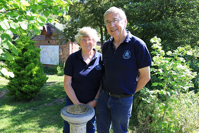 """13 JUN 2021 - PICTURED: Aileen Farnell (Membership Secretary, Harwich Society) and Colin Farnell (Chairman, Harwich Society) at Bobbit's Hole Nature Reserve with sundial, in remembrance of those affected by the Coronavirus Pandemic 2020/21. Photo Copyright © Maria Fowler 2021  PRESS RELEASE Harwich Society installs COVID-19 memorial in Bobbit's Hole  The Harwich Society has installed a memorial to the memory of everyone who passed during the COVID-19 pandemic and whose loved ones were not able to commemorate their passing in the manner in which they would have wished.  The board of Trustees believed that there was a need for such a memorial and, as a result, a sun dial has been erected in the Society's Bobbit's Hole Nature Reserve bearing the inscription, 'However dark the clouds are the Sun is always shining above them '.  Chairman of the Harwich Society, Colin Farnell, says, """"COVID-19 has had an impact on everyone who has lost someone close to them whether it was as a result of the disease or not. No one has been able to commemorate the end of a life in the manner that they would have wished and this memorial is for everyone who has found themselves in this position.""""  The inscription was suggested by one of the Harwich Society's trustees who heard the late Dr. Perry use the words in an address given in Saint Nicholas Church in 2000.  """"We wanted a memorial that would reflect the need and would be appropriate for everyone,"""" continued Colin Farnell. """"A sun dial is timeless and the inscription offers hope at a difficult time. We hope it will provide a point of comfort.""""  A bench is to be installed adjacent to the memorial.  An official unveiling is to be arranged once COVID-19 restrictions are no longer in place.  For further information please contact  Colin Farnell on 01255 553610 Garry Calver on 01255 551940"""