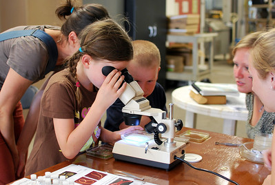 A girl checks out some aquatic invertebrates under the microscope as undergraduate students Carly Broshat and Cristin Fitzpatrick explain what she's seeing.