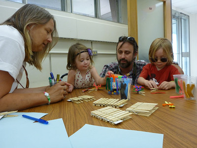 Carol Jenkins-Espinoza helps a couple of young visitors make their clothespin dragonflies.