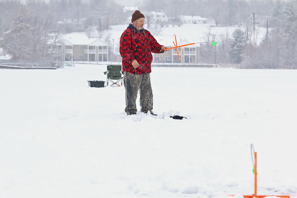 . A little snow and temperatures in the low 30\'s did not stop Bruce Maki of Fitchburg from getting out on the ice at Lake Whalom to a little ice fishing. After catching a yellow belly perch he reset his line.  SENTINEL & ENTERPRISE/JOHN LOVE