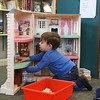 They Ayer Library's childrens room was full of kids having fun just before story time started with Childrens Librarian Amy Leonard on Thursday morning. Playing with the dollhouse at the library as he waits for story time is Matthew Oliver, 2, of Harvard. SUN/JOHN LOVE