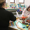 They Ayer Library's childrens room was full of kids having fun just before story time started with Childrens Librarian Amy Leonard on Thursday afternoon. Playing with the toy trains is Mila Santoni, 2, with her mom Raquel Santoni both of Ayer. SUN/JOHN LOVE