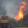 Havre Daily News/Floyd Brandt <br /> <br /> Bulldozers attaches the fire as it flares up at Sucker Creek Road Thursday