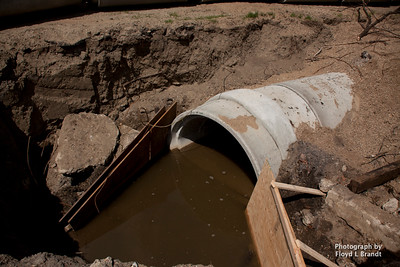 Havre Daily News/Floyd Brandt  the unfinished work    open pits Concret drainage pipe waits to put into the ground Tuesday.